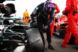 Hamilton inspects his punctured tyre in parc ferme.