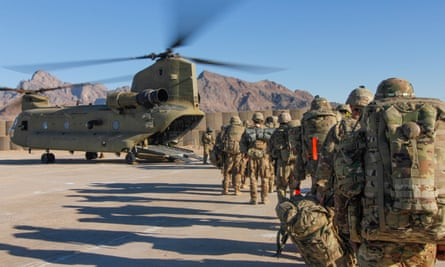US soldiers wait to board a Chinook helicopter