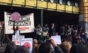 About 200 people protesting against the Australian Border Force operation block the intersection of Flinders Street and Swanston Street in Melbourne on Friday.