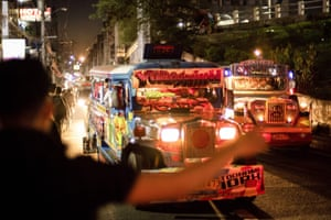 A commuter hails a jeepney during rush hour.