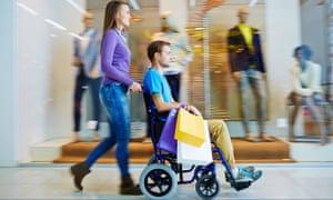 Young woman pushing young man in wheelchair