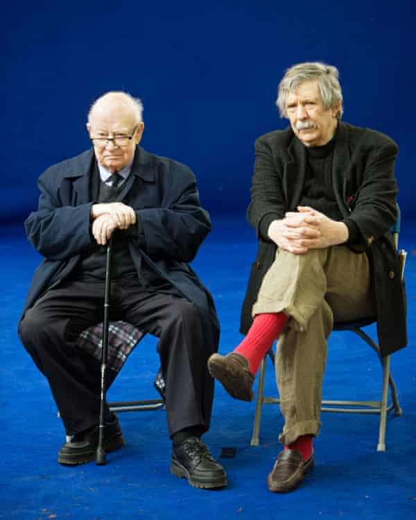 Jim Haynes and John Calder, who is holding a walking stick sitting on chairs on a blue stage