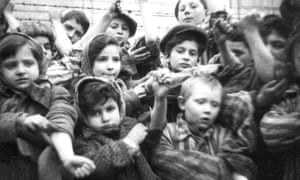 Children show their tattooed identification numbers during the liberation of Auschwitz