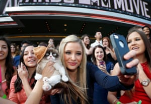 Grumpy Cat gets her photo taken with a fan as she arrives at the 2014 MTV Movie Awards in Los Angeles, California April 13, 2014