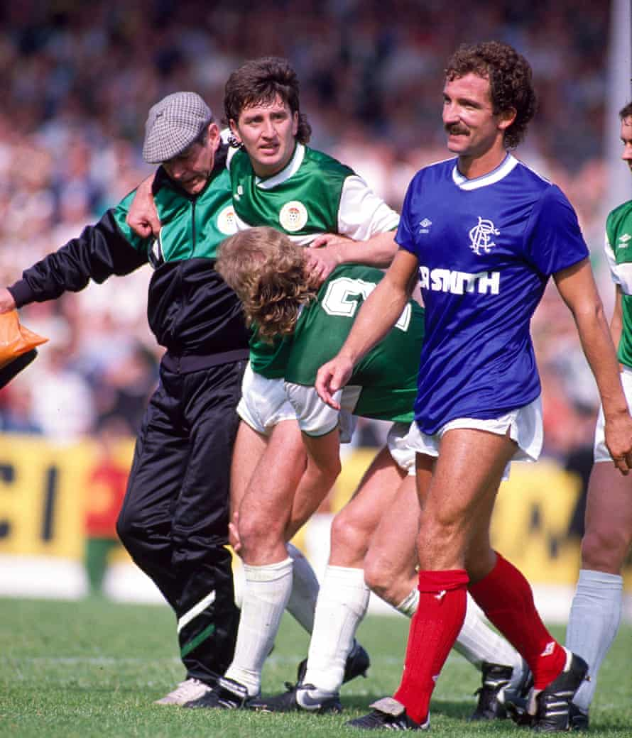 George McCluskey of Hibs is helped off the pitch with a serious knee injury, the result of a challenge from Rangers player-manager, who accompanies him off the field with a smile.