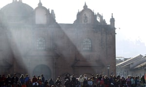 People wait for the Cathedral to open where Mass will be held, as the sun rises in Cuzco Peru
