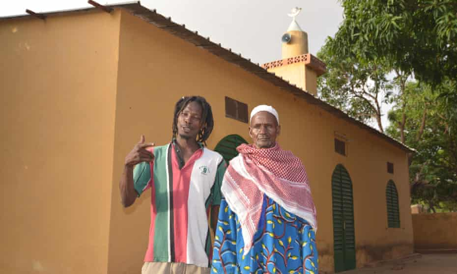 A rastafarian stands with Lassa's Imam outside the village mosque.
