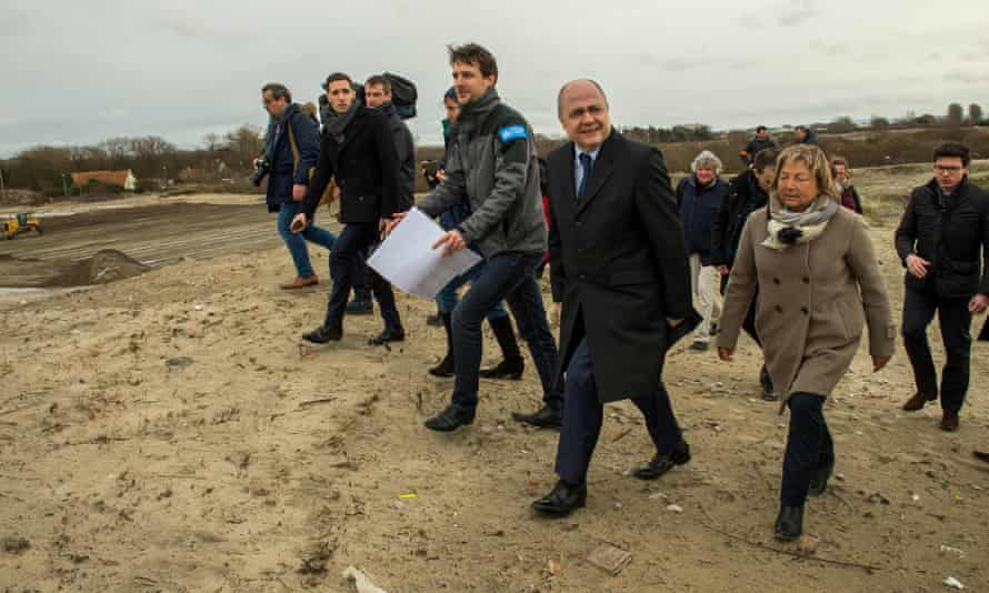 """Bruno Le Roux (2nd R) visits the former refugee camp of """"La Lande"""" with Bouchart to see the site's remediation project."""
