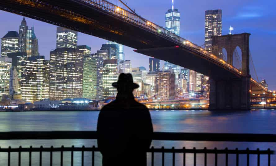 Man standing before Brooklyn bridge and view of lower Manhattan.