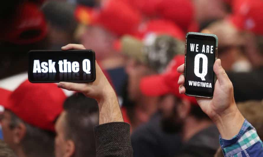 Trump supporters hold up their phones with QAnon messages at a campaign rally at the Las Vegas convention center, 21 February 2020.