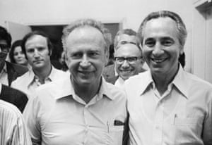 Peres and another man, both smiling and in light-coloured shirts, at the front of a group of people