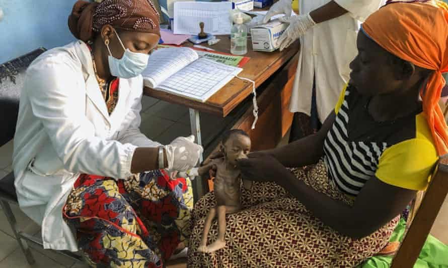 Danssanin Lanizou, 30, holds her month-old baby as a nurse inserts a drip to treat her malnutrition at Houndé hospital in Tuy, Burkina Faso.