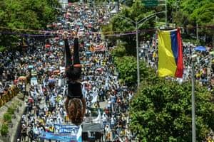 A demonstrator dangles from a slackline in Medellín