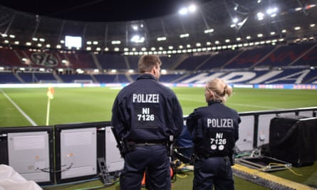 Two German police officers stand guard in front of the empty HDI Arena in Hanover after the friendly between Germany and the Netherlands was called off.