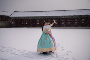 Seoul, South Korea: Visitors wearing traditional hanbok dress pose for selfies in the snow at Gyeongbokgung palace