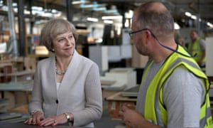Theresa May speaks with a worker