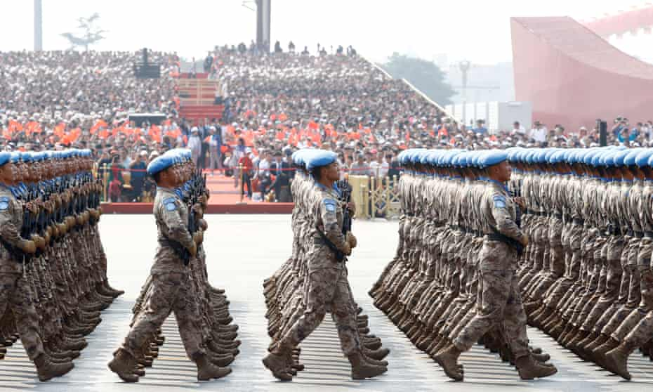 Chinese troops march in formation past Tiananmen Square.