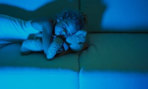 Little girl lying on sofa cuddling with teddy bear, blue light of televisionAWTTE1 Little girl lying on sofa cuddling with teddy bear, blue light of television