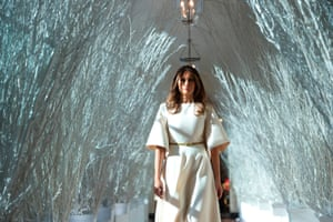 First lady Melania Trump walks through white, frosted branches lining the east wing