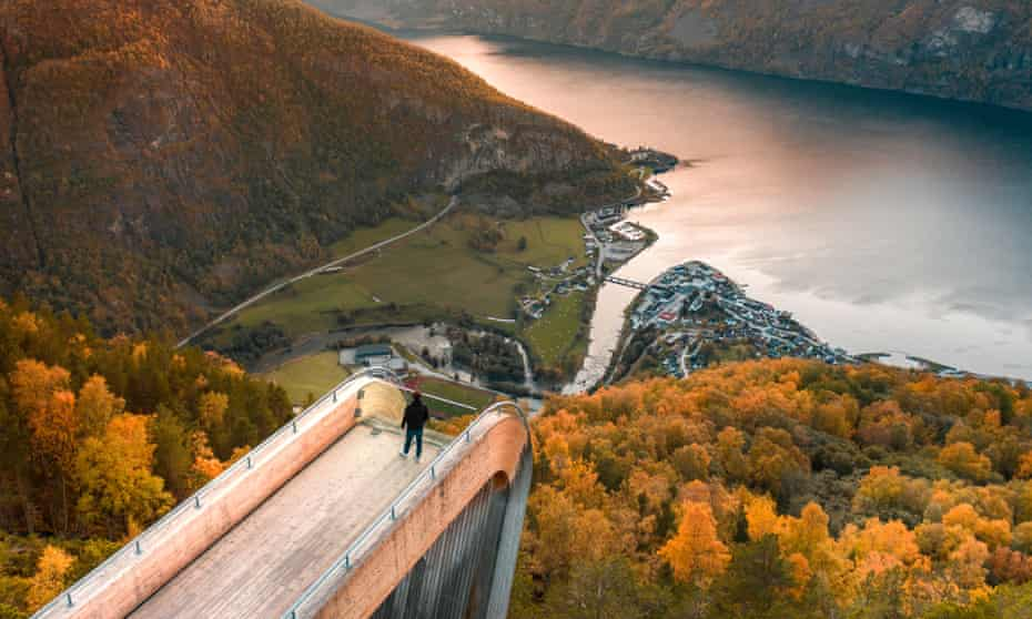 A tourist views Aurlandsfjord from the Stegastein lookout in Norway, at sunset.