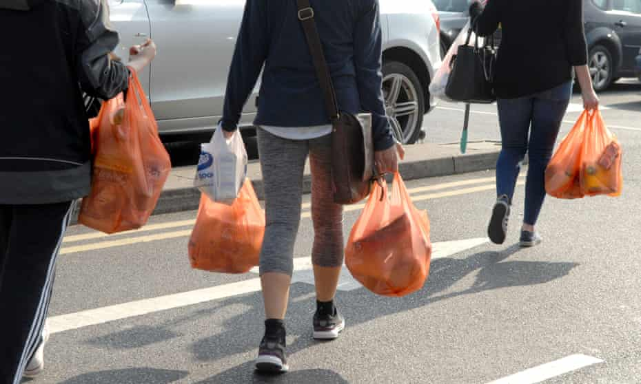 Shoppers carrying plastic bags across a supermarket car park