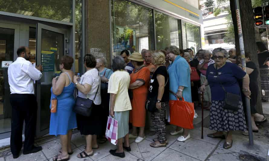 People wait outside a bank in Athens to receive part of their pensions on Thursday.