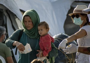 A woman with a baby holds a document before entering the new temporary refugee camp in Kara Tepe, on the island of Lesbos.