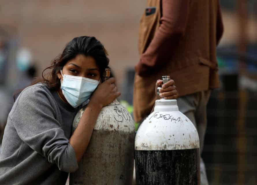 A woman in Kathmandu holds on to oxygen cylinders