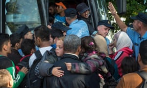 Migrants take a bus to the Hungarian border from a refugee camp in Opatovac, Croatia