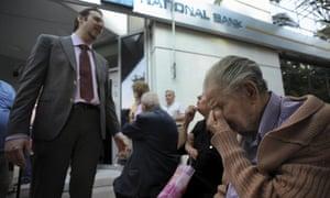 一位银行经理向在希腊国家银行分行外等候的养老金领取者解释了这种情况,希望得到他们的退休金。