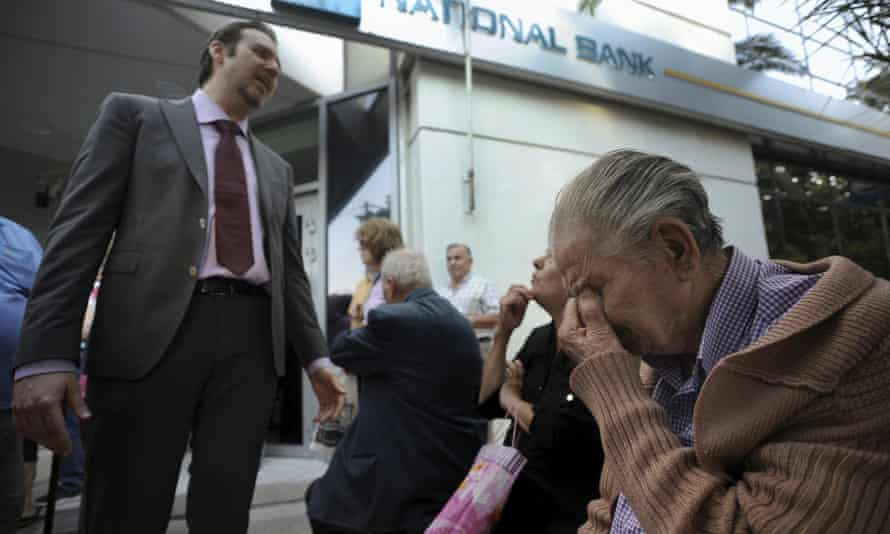 A bank manager explains the situation to pensioners waiting outside a branch of the National Bank of Greece hoping to get their pensions.