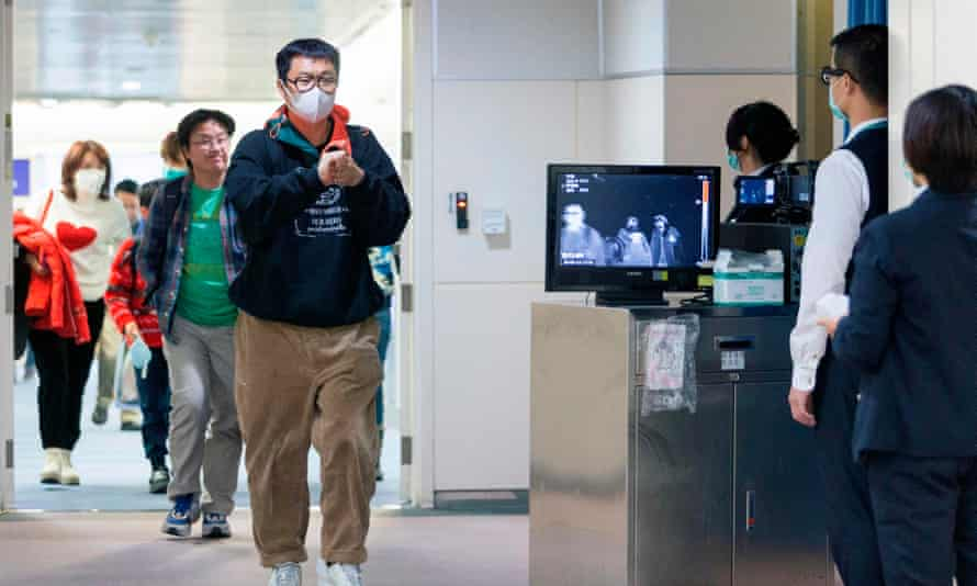 Officials use thermal scanners to screen passengers arriving in Taiwan on a flight from Wuhan