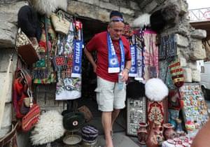 A football fan emerges from a souvenir shop wearing a Chelsea scarf in Baku, Azerbaijan