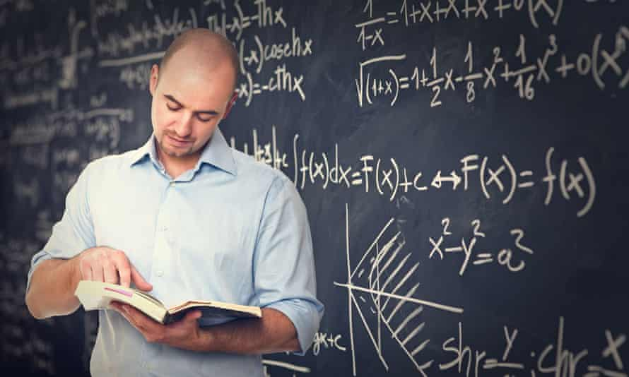 teacher reading a book by a blackboard