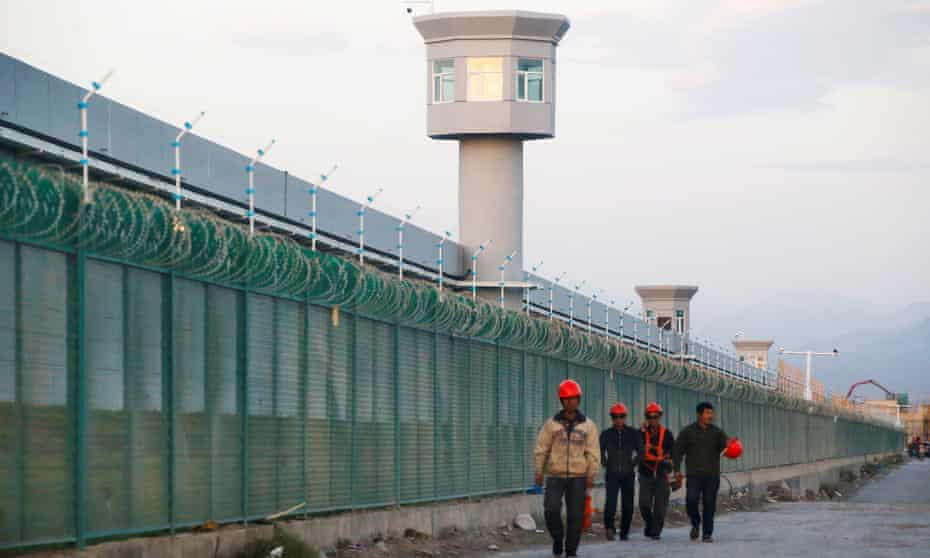 Workers walk by the perimeter fence of what is officially known as a vocational skills education centre in Dabancheng in Xinjiang.