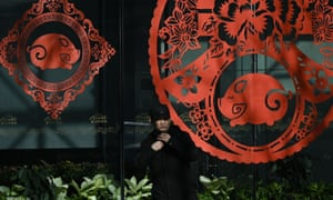 A man stands in front of windows, adorned with festive decals to welcome the Lunar New Year of the Pig, at the entrance of a mall in Beijing today.