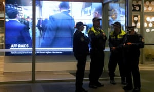 Policemen and women stand in front of a television screen at the main entrance to the ABC building during the AFP raid on Wednesday