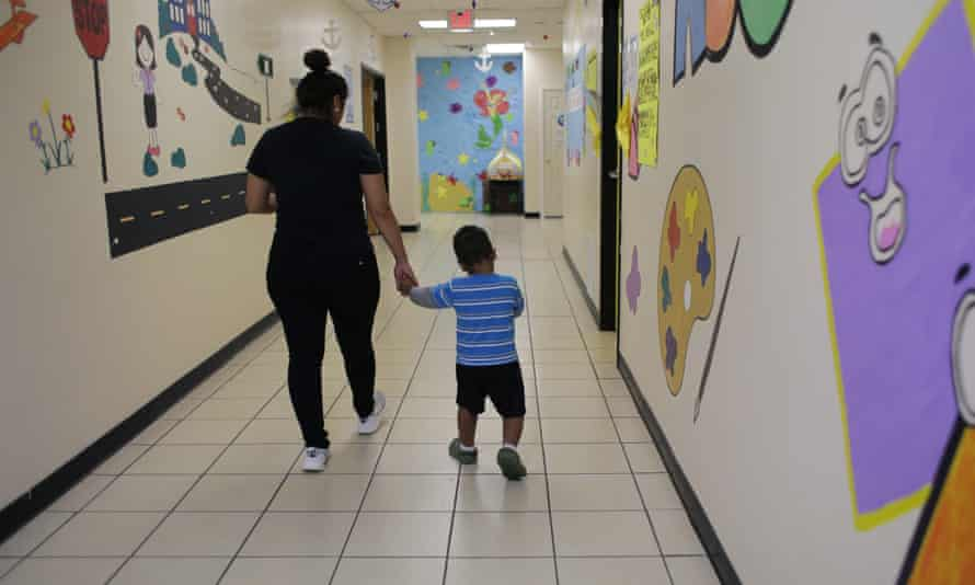A young migrant boy walks with a Comprehensive Health Services caregiver at a 'tender-age' facility for babies, children and teens, in San Benito, Texas.