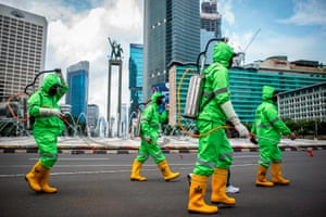 Workers wearing protective suits spray disinfectant, Jakarta