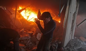 A Syrian man searches for survivors in a building in Douma destroyed by regime airstrikes.