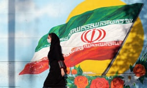 A woman wearing a face mask walks past a mural of Iran's national flag in Tehran.