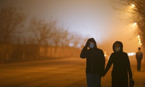 People walk down a street wearing masks on a heavy pollution evening in Beijing, China