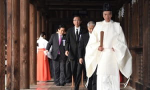 A Shinto priest leads lawmakers at the controversial Yasukuni shrine in Tokyo.