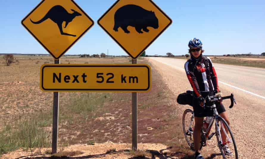 Juliana Buhring standing astride her bike on an empty road next to animal warning roadsigns.