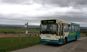 A bus arrives at a rural bus stop