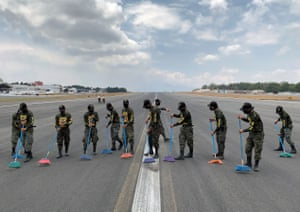 Guatemala City, Guatemala. Members of the army sweep ashes off of the runway of the La Aurora international airport, after authorities suspended its operations due to eruptive activity of the Pacaya volcano