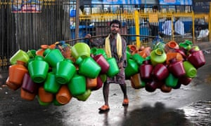 A man carries empty water pitchers