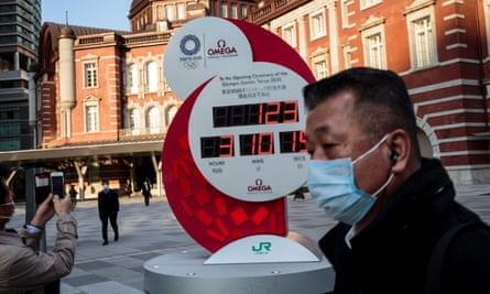 A man wearing a face mask walks past the Olympic countdown clock outside Tokyo station.