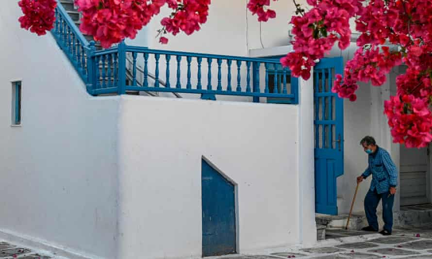 An elderly man wearing a protective facemask enters his house in the Greek island of Mykonos