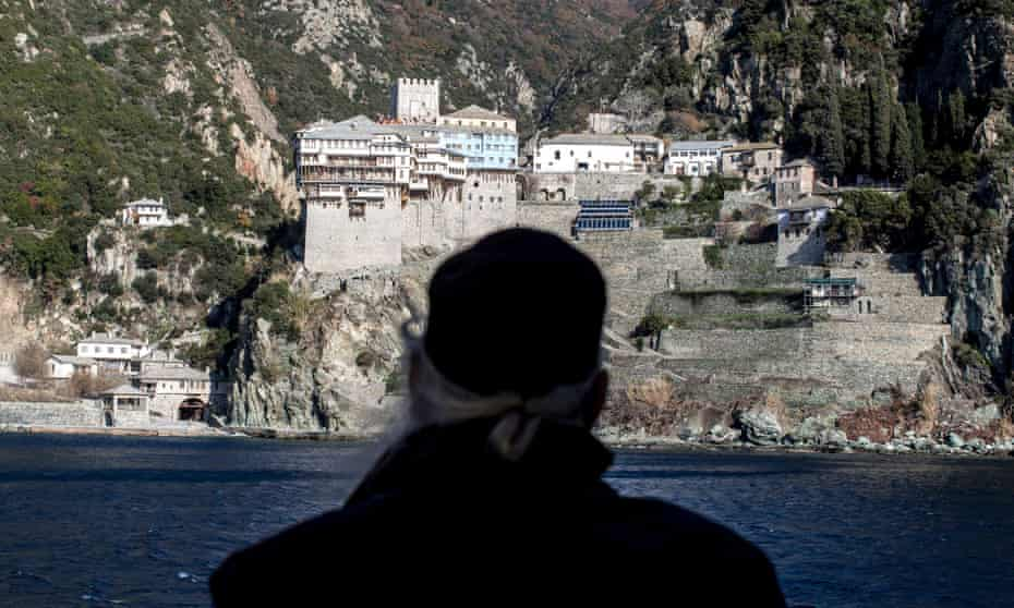 A monk looks toward Dionysiou monastery from a ferry boat before arriving on to Mount Athos in Greece.